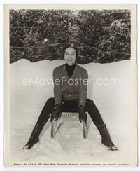 1b039 CAPUCINE 8.25x10.25 '63 great publicity shot of her sitting on a sled outside in the snow!