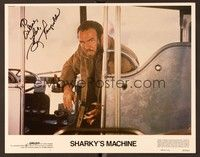 5g071 SHARKY'S MACHINE signed LC #1 '81 by Burt Reynolds, who's close up with gun in front of bus!