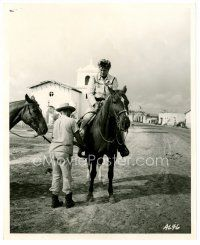 4h049 ALAMO candid 8x10 still '60 John Wayne in costume on horseback helped by crew on set!