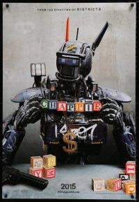 7g123 CHAPPIE teaser DS 1sh '15 close up image of the robot with toy blocks, huge necklace and gun!