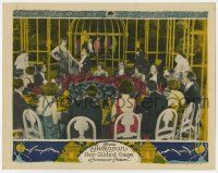 8a071 HER GILDED CAGE LC '22 lots of people at table watch Gloria Swanson by giant bird cage!