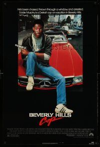 1k078 BEVERLY HILLS COP 1sh '84 great image of cop Eddie Murphy sitting on Mercedes!