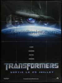 1c954 TRANSFORMERS teaser French 1p 2007 huge robot eye looming over Earth, directed by Michael Bay!