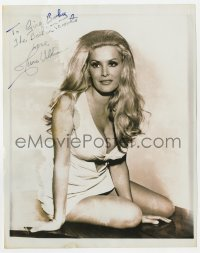 4x827 JUNE WILKINSON signed 8x10 REPRO still 1970s on table in skimpy outfit showing cleavage!